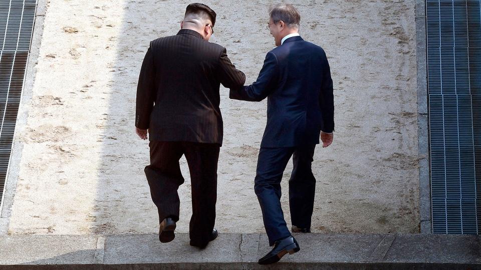 North Korean leader Kim Jong Un, left, and South Korean President Moon Jae-in cross the military demarcation line at the border village of Panmunjom in Demilitarized Zone Friday, April 27, 2018. (Korea Summit Press Pool via AP)