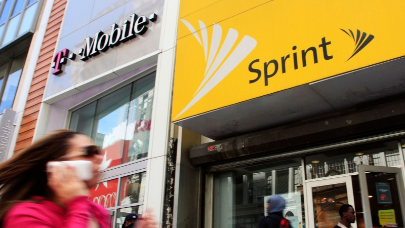In this April 27, 2010 file photo, a woman using a cell phone walks past T-Mobile and Sprint stores in New York. (AP Photo/Mark Lennihan, File)