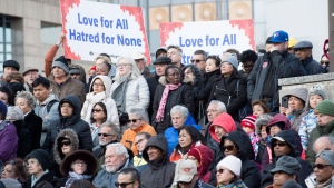 People hold signs and look on at a vigil remembering the victims of Monday's deadly van attack, at Mel Lastman Square in Toronto on Sunday, April 29, 2018. THE CANADIAN PRESS/Frank Gunn
