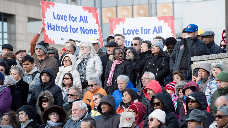 People hold signs and look on at a vigil remembering the victims of Monday's deadly van attack, at Mel Lastman Square in Toronto on Sunday, April 29, 2018. (THE CANADIAN PRESS/Frank Gunn)