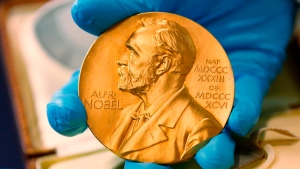 In this file photo dated Friday, April 17, 2015, a national library employee shows the gold Nobel Prize medal awarded to the late novelist Gabriel Garcia Marquez, in Bogota, Colombia. (AP Photo/Fernando Vergara)
