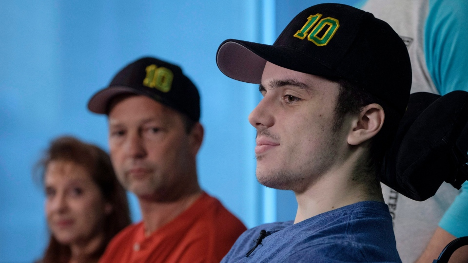 Humboldt Broncos hockey player Ryan Straschnitzki, who was paralyzed following a bus crash that killed 16 people, speaks to the media as his father Tom, centre, and as his mother Michelle, look on in Calgary, Alta., Wednesday, April 25, 2018. (THE CANADIAN PRESS/Jeff McIntosh)