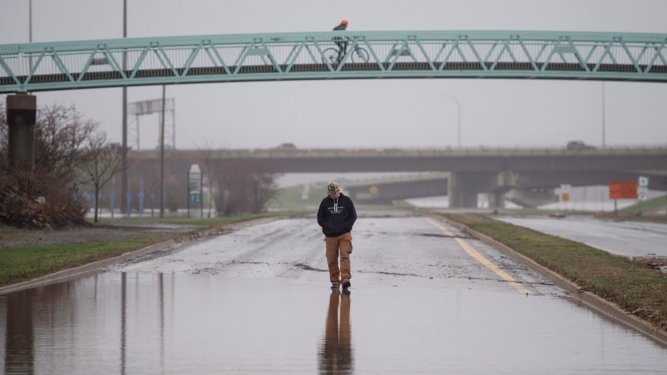 A pedestrian walks along a closed street in downtown Fredericton, N.B. as floodwaters from the St. John River remain level on Monday, April 30, 2018. (THE CANADIAN PRESS/Darren Calabrese)