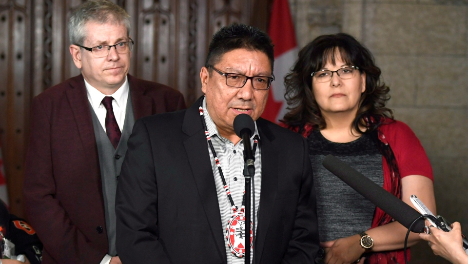 Grand Chief Alvin Fiddler of Nishnawbe Aski Nation speaks to reporters along with NDP MP Charlie Angus and Kim Jonathan, First Vice-Chief of the Federation of Sovereign Indigenous Nations in Saskatchewan, right, about the NDP's motion calling on the House of Commons to officially ask the Pope to apologize to residential school survivors, on Tuesday, May 1, 2018. (THE CANADIAN PRESS/Justin Tang)