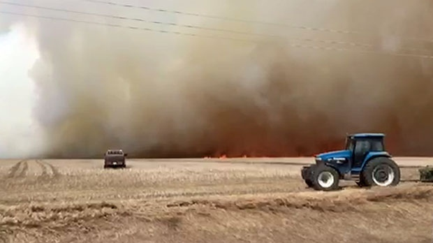 Farmers attempt to create a firebreak during Tuesday afternoon's grass fire near the intersection of Highway 21 and Highway 575 (courtesy: Randy Procyshen)