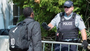 An asylum seeker, claiming to be from Eritrea, is questioned by an RCMP officer as he crosses the border into Canada from the United States Monday, August 21, 2017 near Champlain, N.Y. THE CANADIAN PRESS/Paul Chiasson