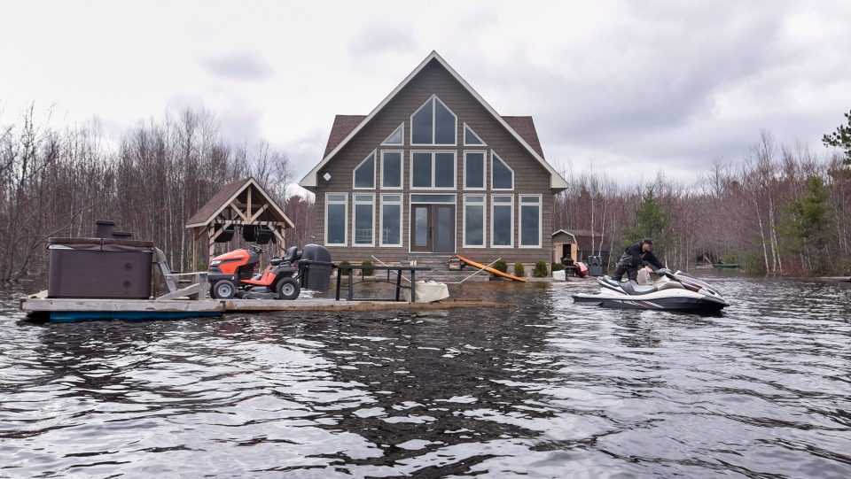 Mike Roy uses a personal watercraft to pull a dock loaded with a hot tub and lawnmower as floodwaters surround his home on Grand Lake, N.B. on Tuesday, May 1, 2018. (THE CANADIAN PRESS/Darren Calabrese)