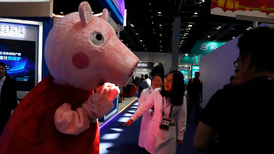 In this April 27, 2018 photo, a woman reacts to a Peppa Pig mascot during the Global Mobile Internet Conference (GMIC) in Beijing, China. (AP Photo/Ng Han Guan)