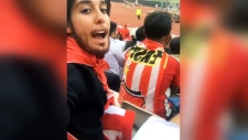 Woman watches soccer in fake beard