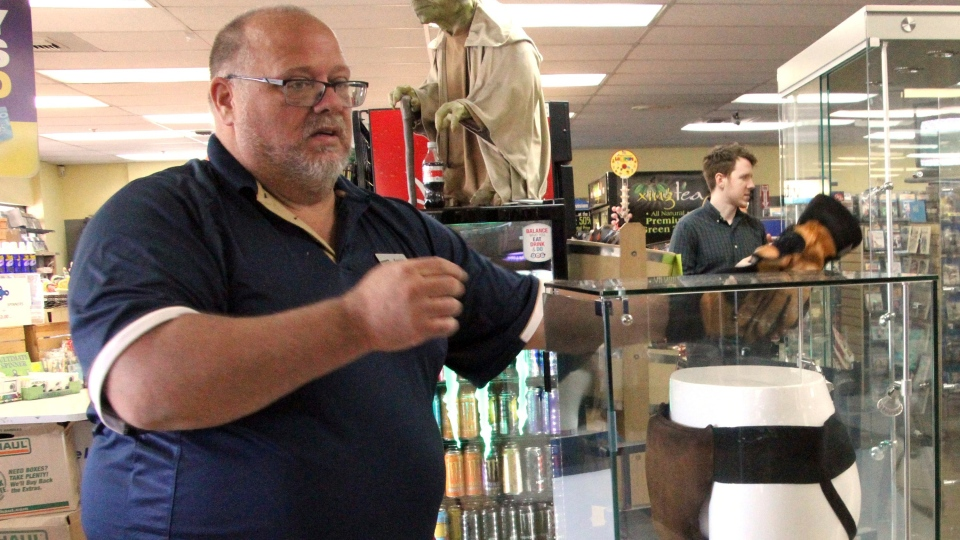 "Blockbuster Alaska General Manager Kevin Daymude moves a display case featuring the jockstrap worn by actor Russell Crowe in the 2005 movie ""Cinderella Man"" at the video store location in Anchorage, Alaska, on Wednesday, May 2, 2018. (AP Photo/Mark Thiessen)"