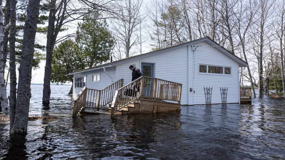 A man carries a bag of clothing before leaving his home as floodwaters from the Saint John River continue rising in Grand Lake, N.B. on May 2, 2018. (Darren Calabrese / THE CANADIAN PRESS)