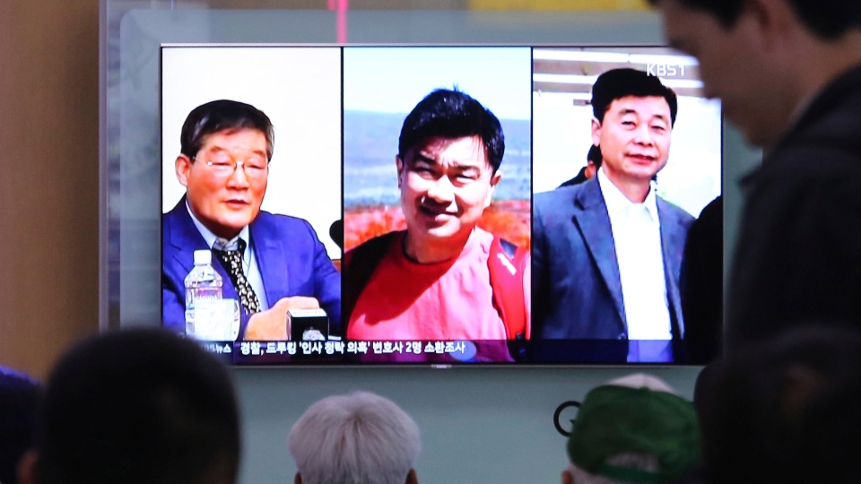 People watch a TV news report on screen, showing portraits of three Americans, Kim Dong Chul, left, Tony Kim and Kim Hak Song, right, detained in the North Korea at the Seoul Railway Station in Seoul, South Korea, Thursday, May 3, 2018. (AP Photo/Ahn Young-joon)