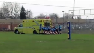 Rugby players from Chateauguay Valley Regional High School push an ambulance off a muddy field on May 2, 2018