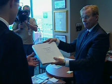 Ottawa Bureau Chief Robert Fife hands the documents labelled 'secret' that were left at CTV's bureau in Ottawa to a government representative.