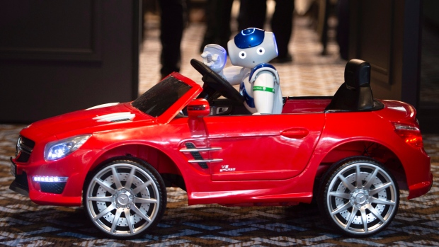 NAO, a humanoid robot, is seen driving a model car