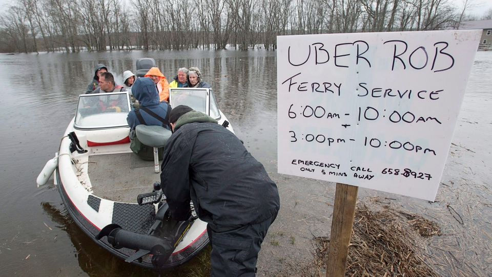 Rob Dekany, known locally as Uber Rob, ferries stranded passengers at Darlings Island, N.B. on Thursday, May 3, 2018 as the Kennebecasis River flooded the only road into the community. Dekaney has been offering the service all week and refuses to accept any payment. THE CANADIAN PRESS/Andrew Vaughan
