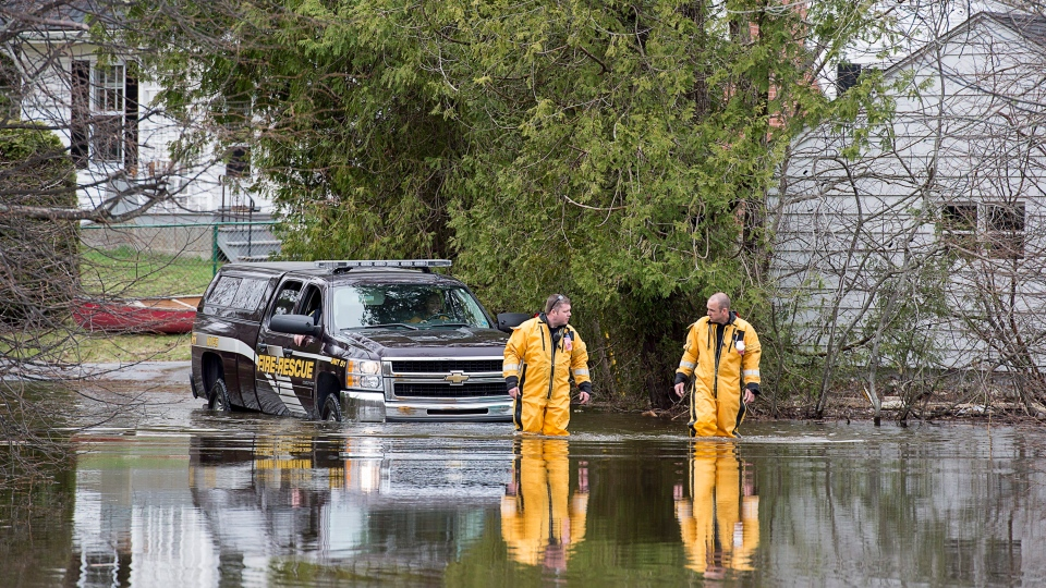 Firefighters head back from checking on residents of an area of Rothesay, N.B. that is cut off by flood waters on Friday, May 4, 2018. THE CANADIAN PRESS/Andrew Vaughan