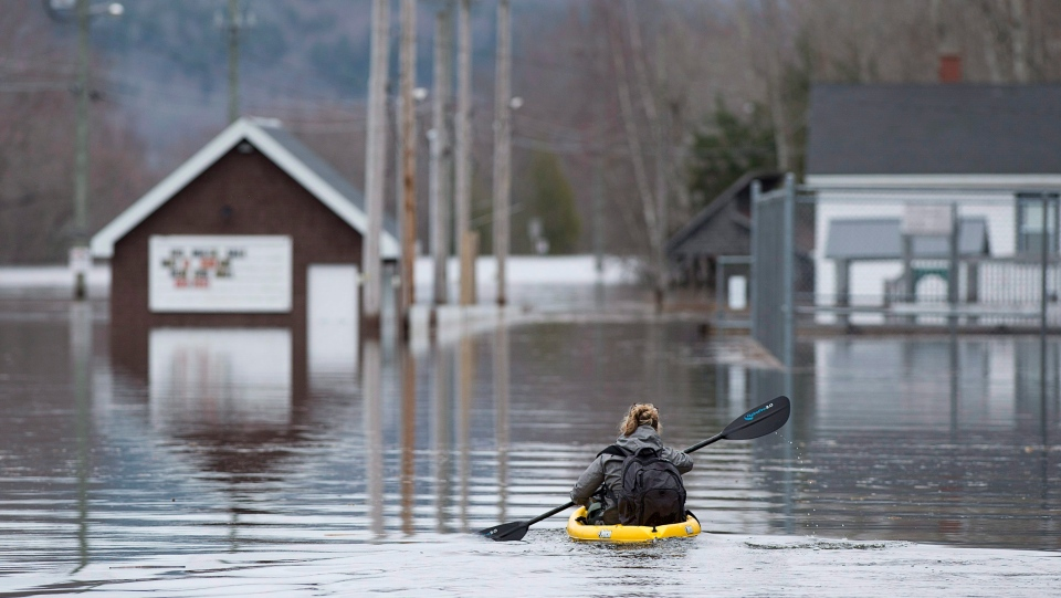 A resident paddles her kayak at Darlings Island, N.B. on Thursday, May 3, 2018 as the Kennebecasis River flooded the only road into the community. THE CANADIAN PRESS/Andrew Vaughan