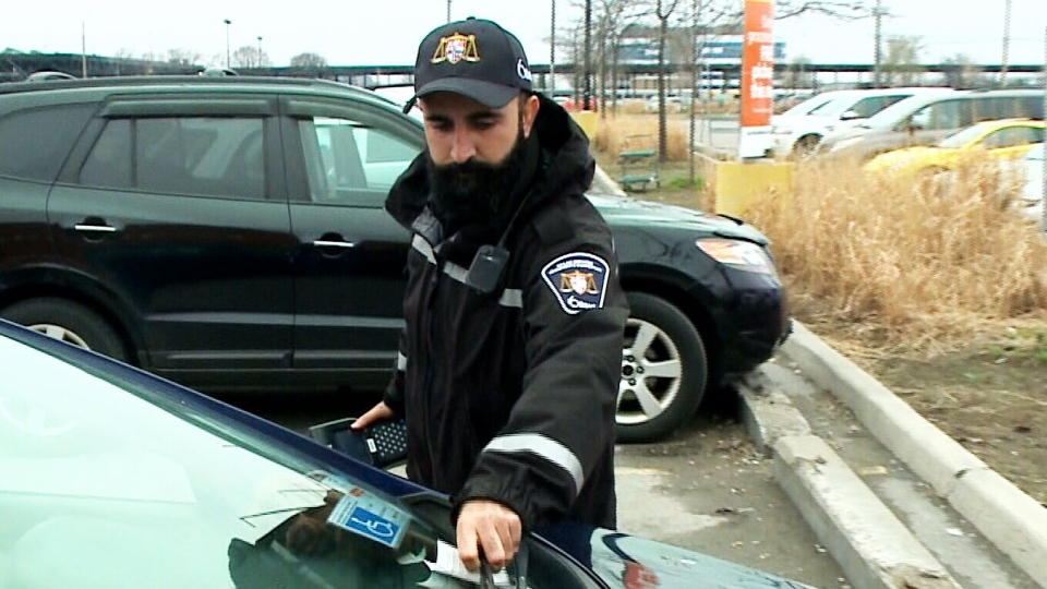 Parking enforcement officer Ahed Khalil tickets a car for an accessible parking violation.