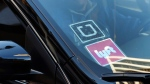 FILE - In this Tuesday, Jan. 12, 2016, file photo, a driver displaying Lyft and Uber stickers on his front windshield drops off a customer in downtown Los Angeles. (AP Photo/Richard Vogel, File)