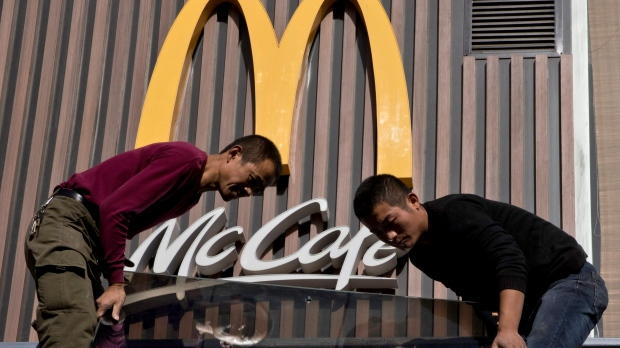 Chinese workers install McDonald's sign in Beijing