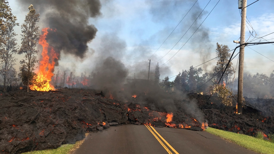 In this Saturday, May 5, 2018, photo provided by the U.S. Geological Survey, lava from Fissure 7 slowly advances to the northeast on Hookapu Street in the Leilani Estates subdivision in Pahoa, Hawaii. (U.S. Geological Survey via AP)