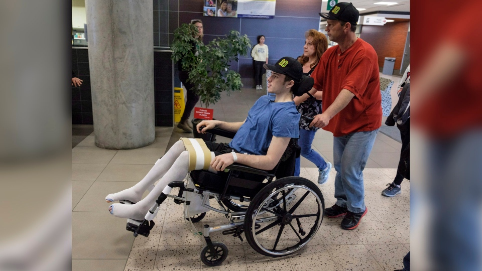 Humboldt Broncos hockey player Ryan Straschnitzki, who was paralyzed following a bus crash that killed 16 people, is wheeled by his father Tom as his mother Michelle, centre, walks beside in Calgary, Alta., Wednesday, April 25, 2018. THE CANADIAN PRESS/Jeff McIntosh