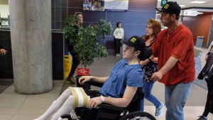Humboldt Broncos hockey player Ryan Straschnitzki, who was paralyzed following a bus crash that killed 16 people, is wheeled by his father Tom as his mother Michelle, centre, walks beside in Calgary, Alta., Wednesday, April 25, 2018.Tom said he woke up early in the morning and was alerted on Twitter that someone using Ryan's name had set up a fake account and was seeking money for a GoFundMe campaign. THE CANADIAN PRESS/Jeff McIntosh