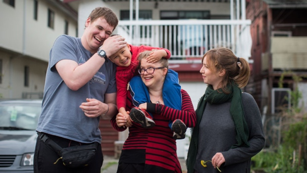 Patrick Caldicott, left, shares a laugh with Laelo Vervecken-Wong, 4, as he's held by his mom Anika Vervecken, centre, while posing for a photograph along with Megan Brydie, right, who all live together in a house, in Vancouver, B.C., on Monday April 30, 2018. THE CANADIAN PRESS/Darryl Dyck