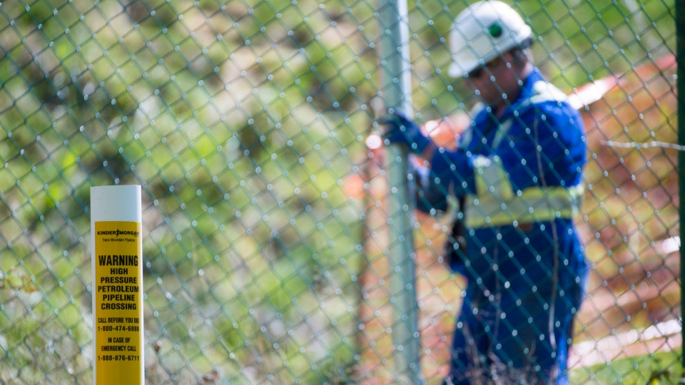 A worker installs new fence posts surrounding the Burnaby B.C., Kinder Morgan site, on Thursday, April 26, 2018. (THE CANADIAN PRESS/Jonathan Hayward)