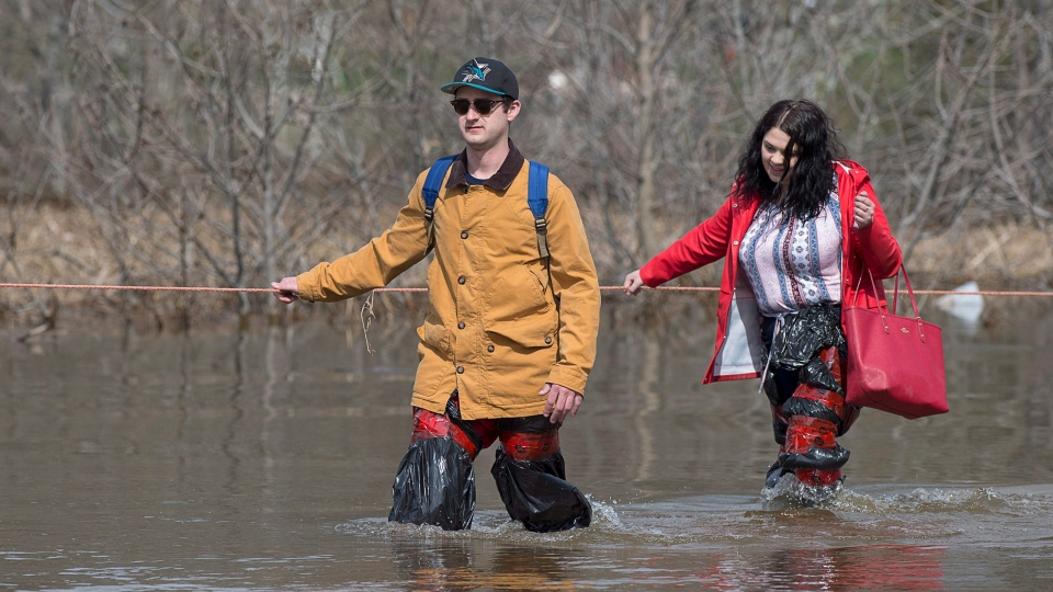 Simon Barton, left, and Chelsea Burley wear make shift waders of garbage bags and packing tape as they cross a flooded road in Saint John, N.B. on Sunday, May 6, 2018. Swollen rivers across New Brunswick are still rising, flooding streets and properties and forcing people from their homes in several communities. (THE CANADIAN PRESS/Andrew Vaughan)