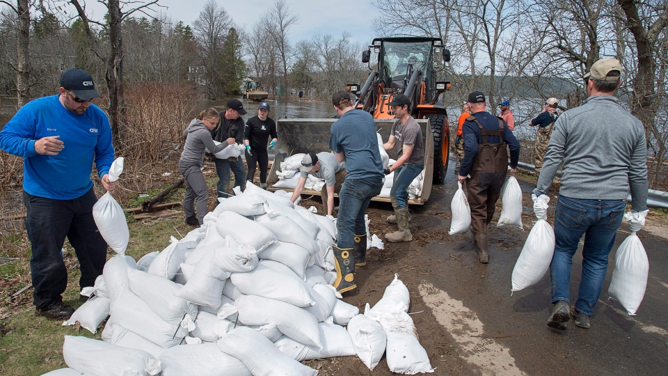 Residents and community volunteers load sandbags in Rothesay, N.B. on Sunday, May 6, 2018. Swollen rivers across New Brunswick are still rising, flooding streets and properties and forcing people from their homes in several communities. (THE CANADIAN PRESS/Andrew Vaughan)