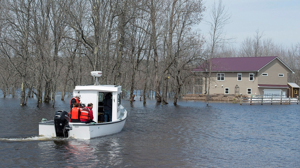 A boat ferries residents to Darlings Island, N.B., cut off by flood waters, on Sunday, May 6, 2018. (Andrew Vaughan/THE CANADIAN PRESS)