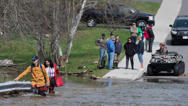 Simon Barton, left, and Chelsea Burley wear make shift waders of garbage bags and packing tape as they cross a flooded road in Saint John, N.B. on Sunday, May 6, 2018. THE CANADIAN PRESS/Andrew Vaughan