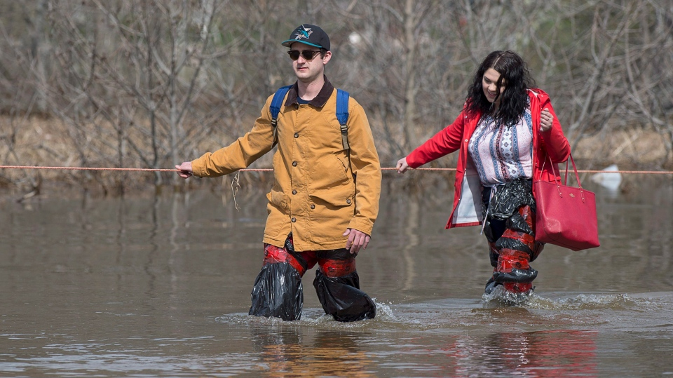 Simon Barton, left, and Chelsea Burley wear makeshift waders of garbage bags and packing tape as they cross a flooded road in Saint John, N.B. on Sunday, May 6, 2018. (THE CANADIAN PRESS/Andrew Vaughan)