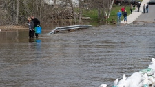 Residents wade across a flooded road in N.B.