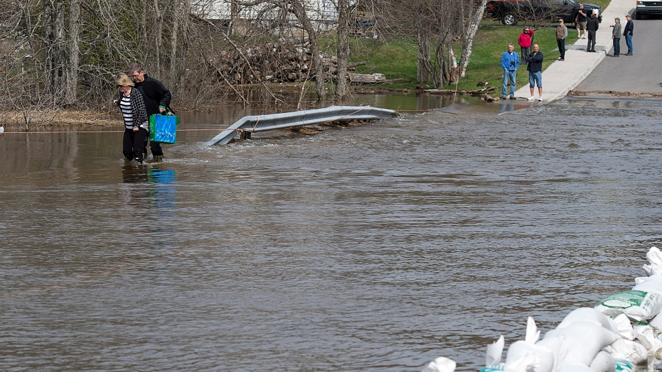 Residents wade across a flooded road in Saint John, N.B. on Sunday, May 6, 2018. (Andrew Vaughan / THE CANADIAN PRESS)