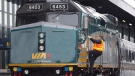 A Via Rail employee climbs aboard a locomotive at the train station in Ottawa on December 3, 2012. (THE CANADIAN PRESS/Adrian Wyld)