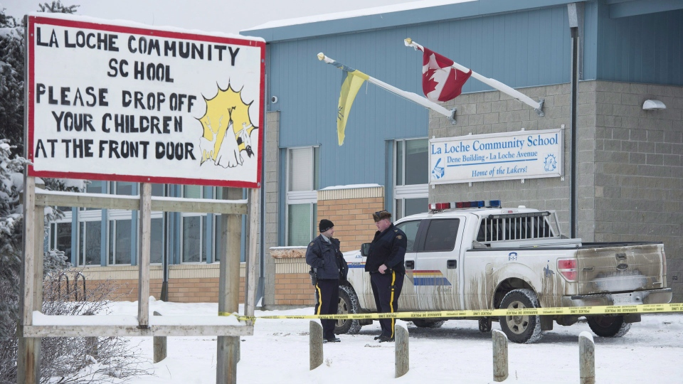 Members of the RCMP stand outside the La Loche Community School in La Loche, Sask. Monday, Jan. 25, 2016. (Jonathan Hayward / THE CANADIAN PRESS)