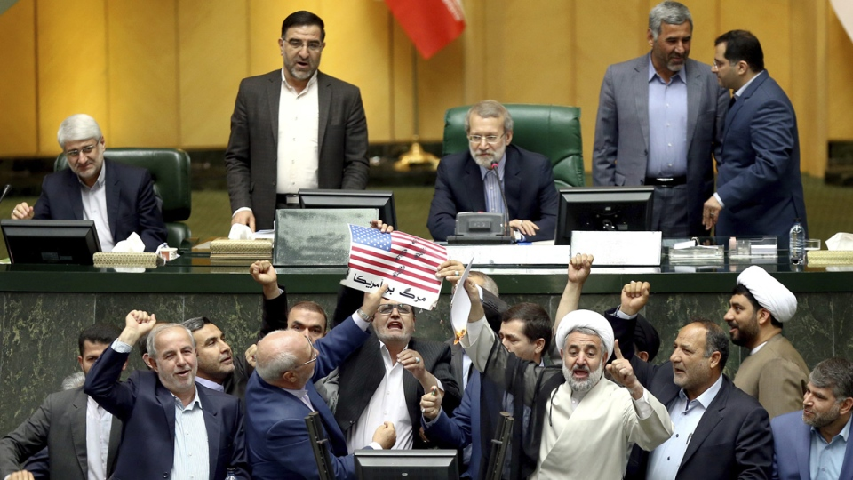 Iranian lawmakers burn two pieces of papers representing the U.S. flag and the nuclear deal as they chant slogans against the U.S. at the parliament in Tehran, Iran, on May 9, 2018. (AP