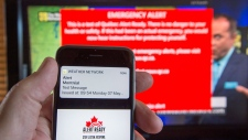 A smartphone and a television receive visual and audio alerts to test Alert Ready, a national public alert system Monday, May 7, 2018 in Montreal.THE CANADIAN PRESS/Ryan Remiorz