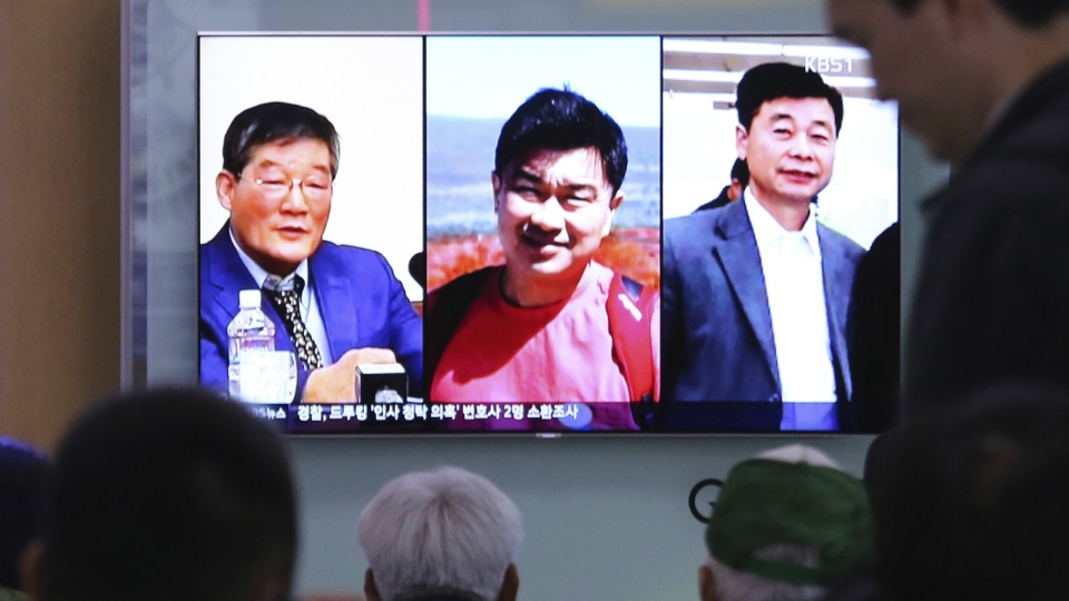 People watch a TV news report on screen, showing portraits of three Americans, Kim Dong Chul, left, Tony Kim and Kim Hak Song, right, detained in the North Korea, at the Seoul Railway Station in Seoul, South Korea on May 3, 2018. (AP Photo/Ahn Young-joon)