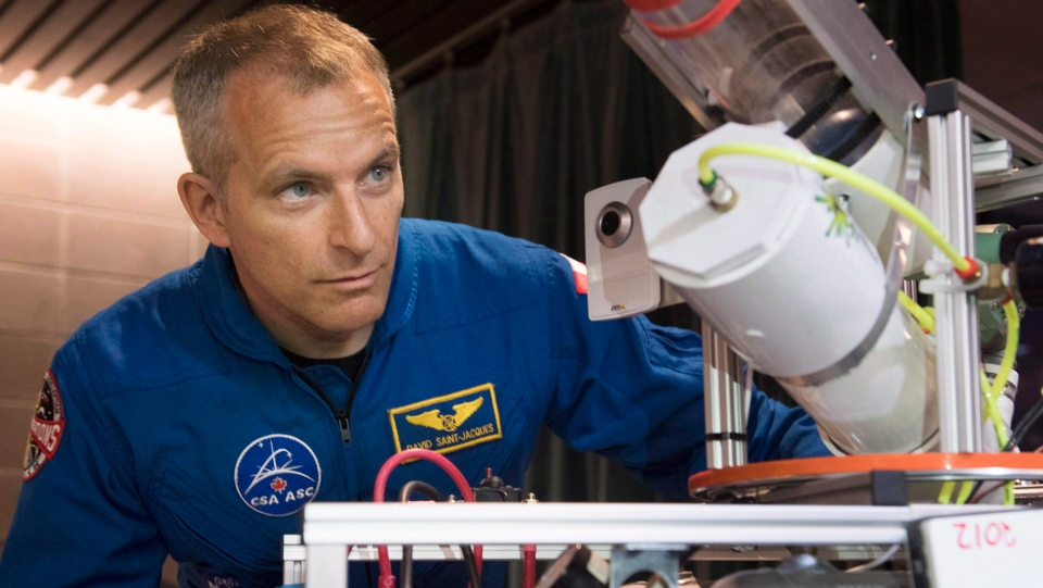 Astronaut David Saint-Jacques looks at a model robot at the FIRST Quebec robotics competition in Montreal, Saturday, March 3, 2018. (THE CANADIAN PRESS/Graham Hughes)