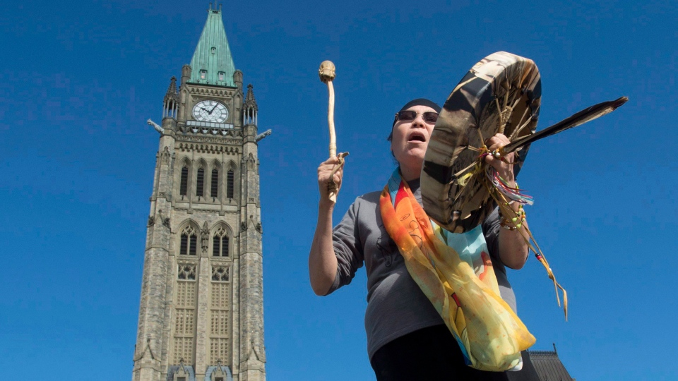 Chief Marcia Brown Martel sings outside the parliament buildings following a government news conference announcing a compensation package for Indigenous victims of the '60s Scoop, in Ottawa on Friday, Oct. 6, 2017. THE CANADIAN PRESS/Adrian Wyld