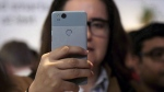 A woman looks at a Google Pixel 2 phone in San Francisco, on Oct. 4, 2017. (Jeff Chiu / THE CANADIAN PRESS / AP)