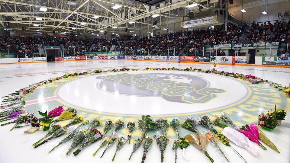 Flowers lie at centre ice as people gather for a vigil at the Elgar Petersen Arena, home of the Humboldt Broncos, to honour the victims of a fatal bus accident in Humboldt, Sask. on Sunday, April 8, 2018.  THE CANADIAN PRESS/Jonathan Hayward