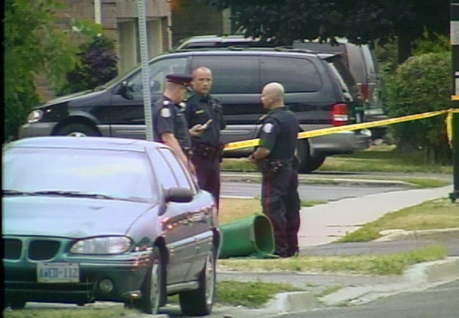 Toronto police investigate the scene of the double-murder in Scarborough on Wednesday, July 4, 2007.