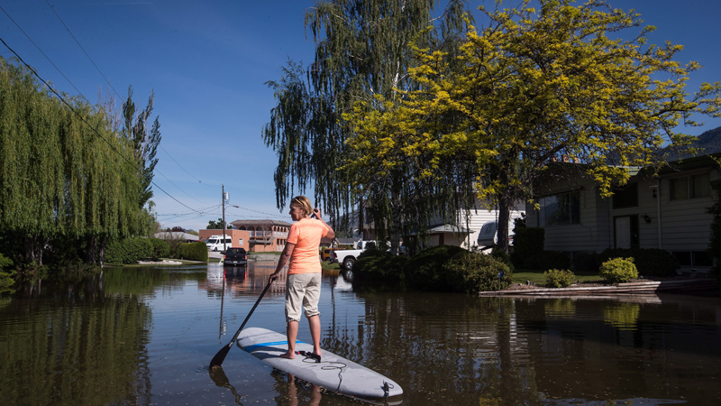 Trudy Johnston uses a stand up paddleboard to navigate the flooded street in her neighbourhood as water from Osoyoos Lake floods the street and properties, in Osoyoos, B.C., on Saturday May 12, 2018. (THE CANADIAN PRESS/Darryl Dyck)
