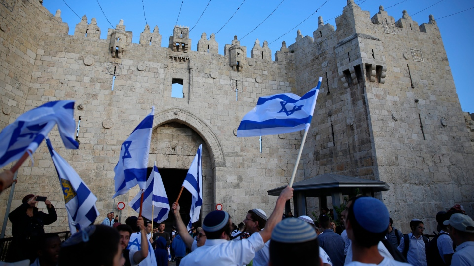 Israelis wave national flags outside the Old City's Damascus Gate, in Jerusalem, Sunday, May 13, 2018. Israel is marking the 51st anniversary of its capture of east Jerusalem in the 1967 Middle East war. (AP Photo / Ariel Schalit)