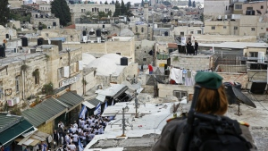 An Israeli border police officer watches as Israelis wave national flags inside the Old City's Damascus Gate in Jerusalem, Sunday, May 13, 2018. (AP Photo/Ariel Schalit)